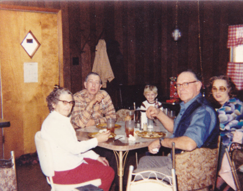 A blonde headed Shane Draper as a kid sitting with his family. Shane's Grandfather is in the tan shirt, and his Grandmother is in the blue blouse.